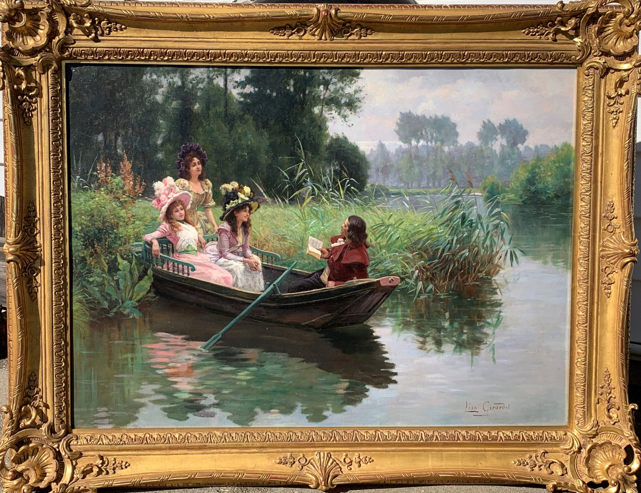 Three ladies in dresses sit aboard a small rowing boat on a lake with a gentleman reading from a book by Leon Girardet