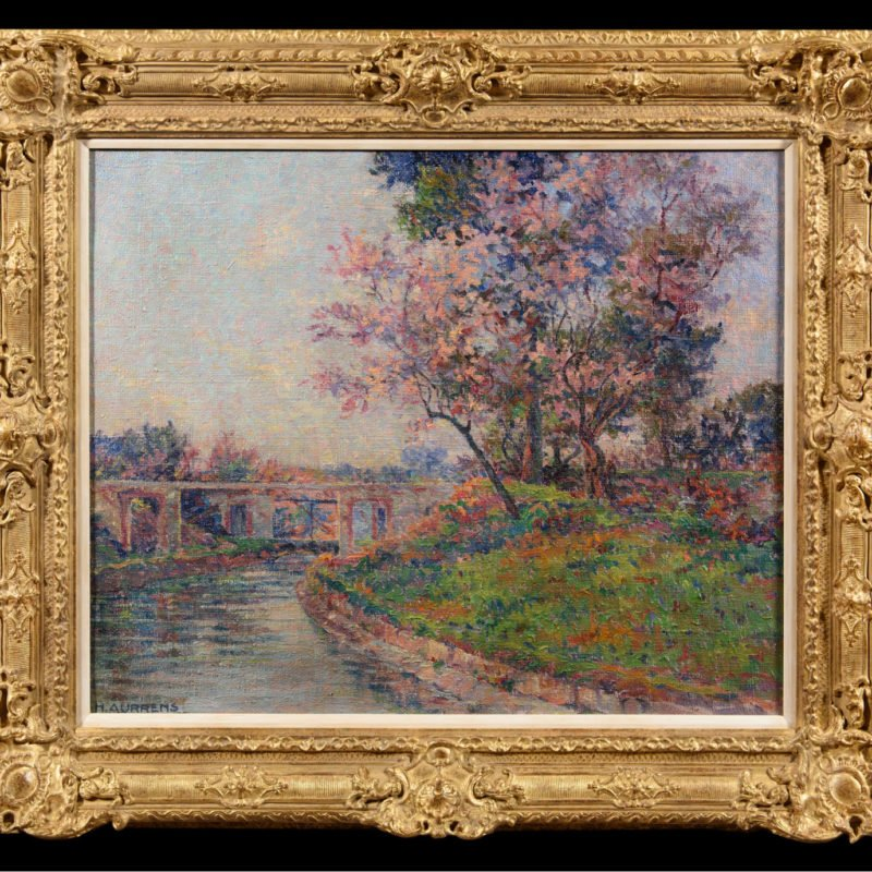 landscape with a river next to a bank with green grass and pink trees on it. There is a bridge in the background
