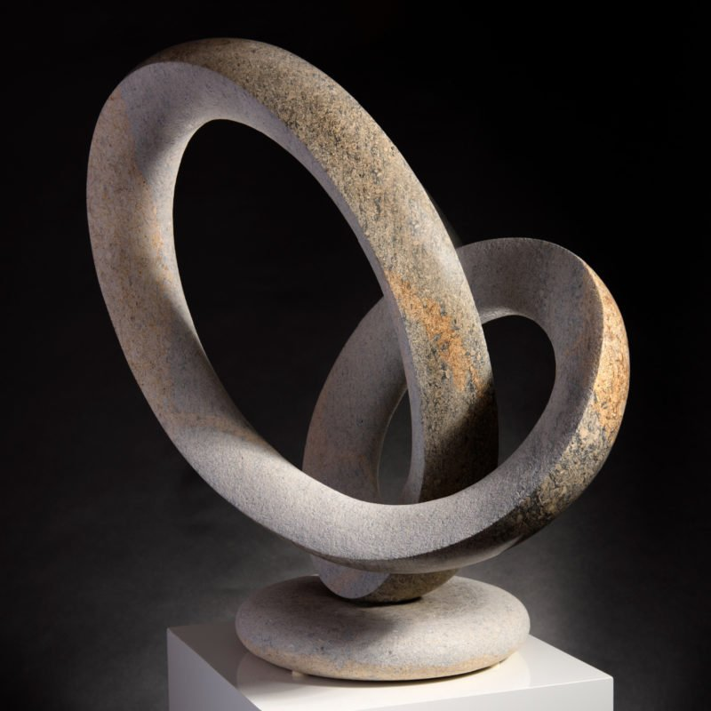 Abstract limestone sculpture with the stone looping in between each other by Michael Thacker