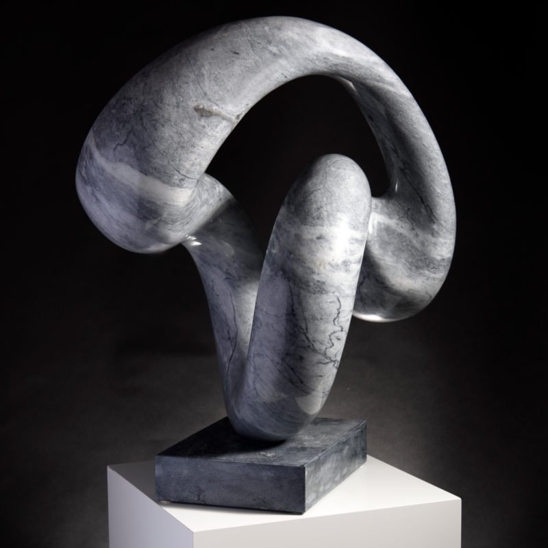 Abstract grey limestone sculpture that creates a loop entangled between each other by Michael Thacker