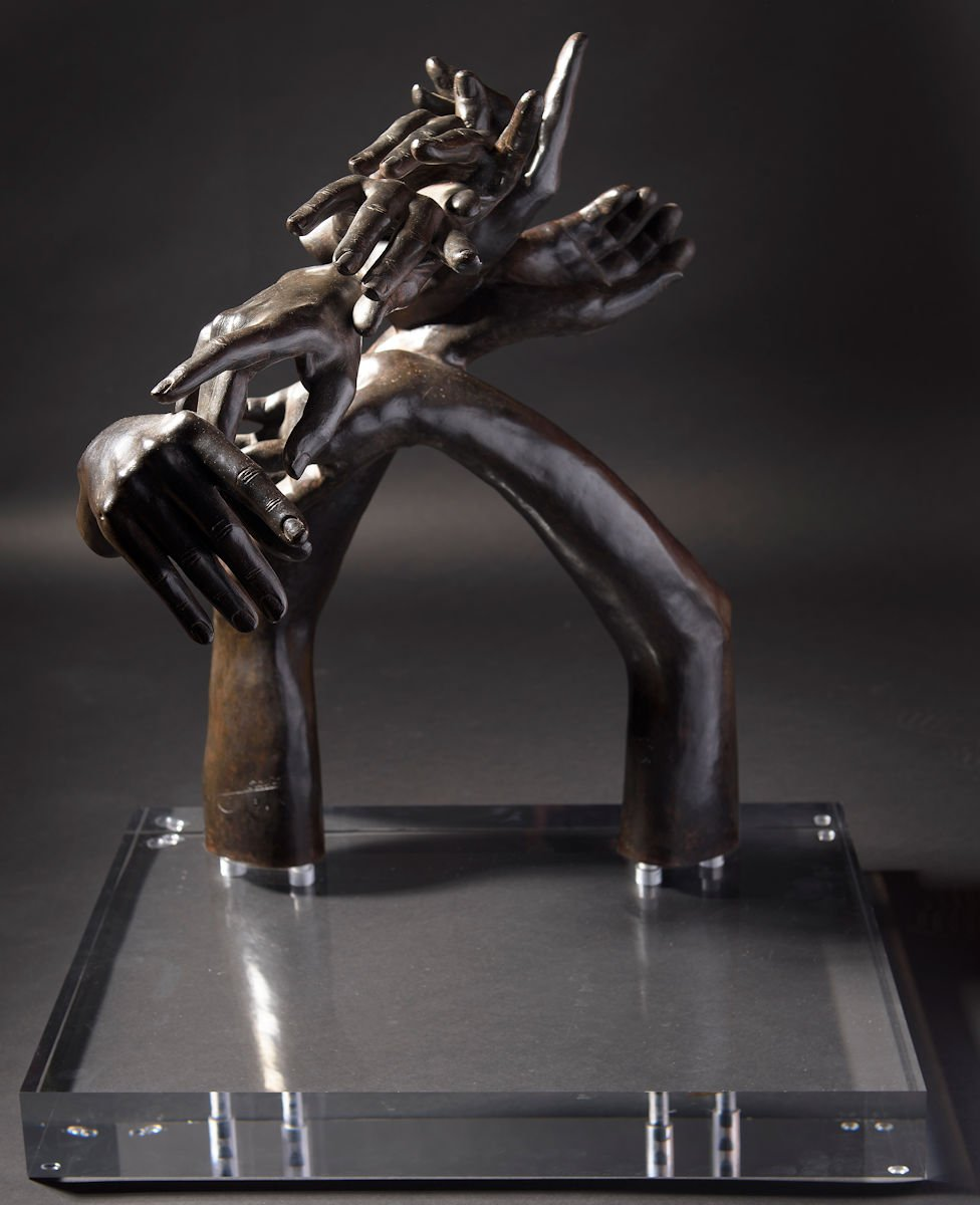 sculpture of two arms interlocking with several hands