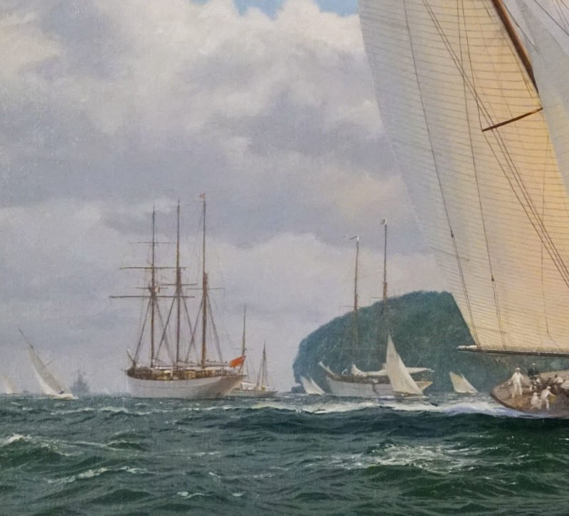 Sail boats following racing yachts with island in background