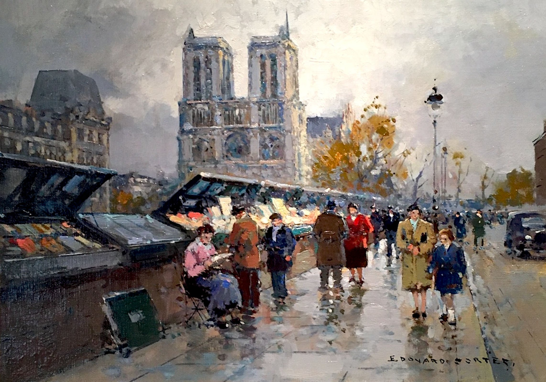 A street with stalls on the side and pedestrians walking past with Notre Dame in the background
